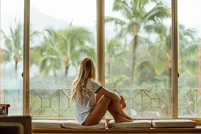 jeune femme assise devant la fenêtre